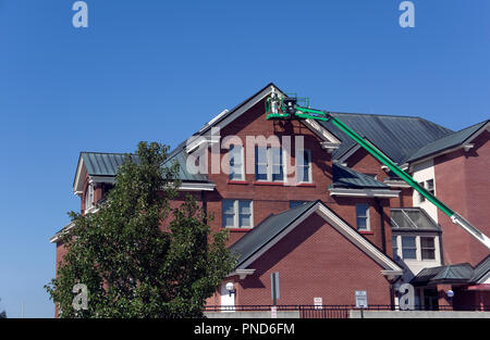 Man on mobile aerial work platform painting high trim on Two Rivers, WI City Hall - Stock Image