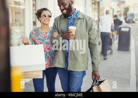 Smiling young couple with coffee and shopping bags walking along storefront - Stock Image