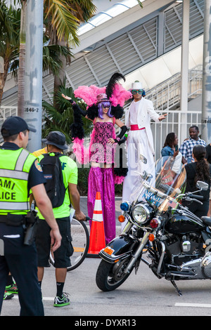 Male and female stilt walkers in colorful costumes at 2014 Mercedes-Benz Corporate Run in Miami, Florida, USA. - Stock Image