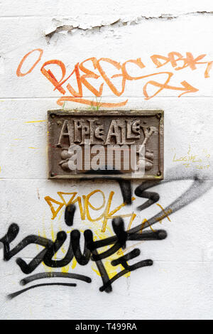 Apple Alley sign on white wall surrounded by graffiti in Frome Somerset UK - Stock Image