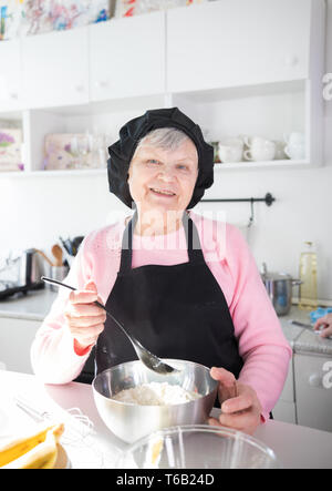 Smiling old woman making pancakes in the kitchen - Stock Image