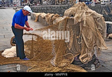 FISHERMAN REPAIRING FISHING NETS. HONFLEUR, NORMANDY, FRANCE, JUNE 2014. Local fisherman repairing his fishing nets on the Quayside at Honfleur, Norma - Stock Image