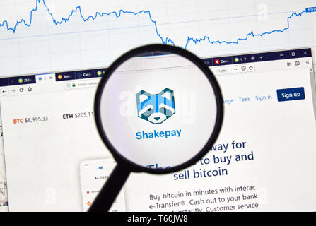MONTREAL, CANADA - APRIL 26, 2019: Shakepay cryptocurrency digital assets exchange logo and home page on a laptop screen under magnifying glass. - Stock Image
