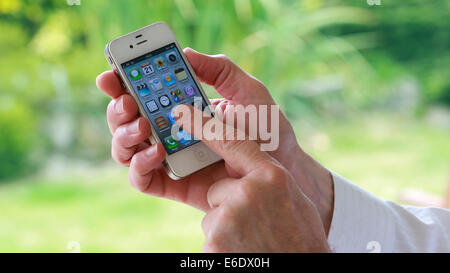 A man's hand holding an i-phone pressing an app on the screen. - Stock Image
