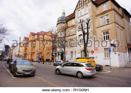 Poznan, Poland - March 8, 2019: Parked cars and driving on a road by a hostel and small shop on the Slowackiego street. - Stock Image
