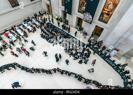 London, UK. 16th February 2019. Campaign group BP or Not BP perform a short theatrical presentation in the Assyrian galleries of the British Museum on the 16th anniversary of the 2003 invasion of Iraq, Dressed as BP executives they boast how their small contribution to the museum funds generates so much positive publicity for BP, and urge the museum to end BP sponsorship, which covers up their polluting activities which cause climate change and their neocolonial complicity in the Iraq war to open up Iraqi oil reserves. Credit: Peter Marshall/Alamy Live News - Stock Image