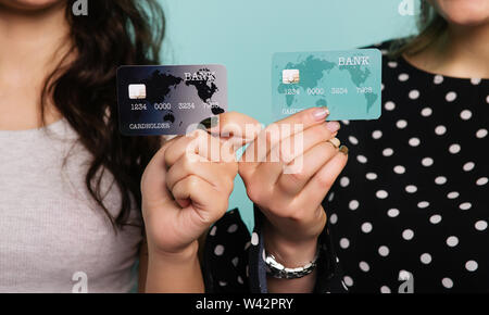 Two happy women in dresses posing together while showing credit cards at camera on blue background - Image - Stock Image