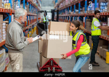 Warehouse manager noting on clipboard while female worker carrying cardboard boxes - Stock Image