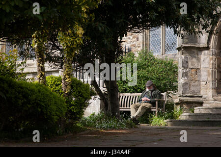 Man takes an afternoon nap outside St. Clement's church in Hastings Old town. - Stock Image