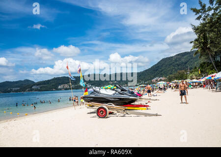 Phuket, Thailand - 12th November 2018: Jetskis and tourists on Patong beach. This is the most popular resort on the island. - Stock Image