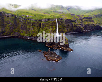 A dramatic waterfall cascades down the north coast of Tanaga Island in the Aleutian Islands, Alaska. - Stock Image
