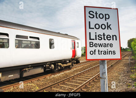 Stop Look Listen Beware of Trains sign on the edge of train tracks in rural norfolk as the diesel train passes - Stock Image