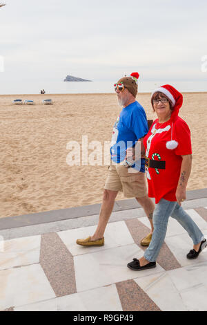 Benidorm, Costa Blanca, Spain, 25th December 2018. British tourists dress for the occasion on Christmas Day in this favourite getaway destination for Brits escaping the cold weather at home. Temperatures will be in the mid to high 20's Celsius today in this mediterranean hotspot. Middle aged couple wearing Christmas Jumpers walking outside on the sea front promenade on Levante Beach with christmas pudding comedy glasses, - Stock Image