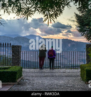 A mature couple stands at a fence looking out over the landscape of Ronda at sunset; Ronda, Malaga province, Spain - Stock Image