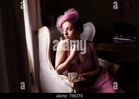 Attractive young woman in 1920s flapper dress sitting in dark room near windows, with clair obscur light effect - Stock Image