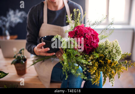 A midsection of young creative woman with a coffee arranging flowers in a flower shop. A startup of florist business. - Stock Image