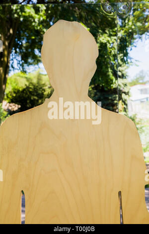 Plywood cutout of a male figure against a reflective mirror background outdoors - Stock Image