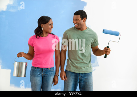 African American smiling couple next to half painted wall with paint supplies - Stock Image