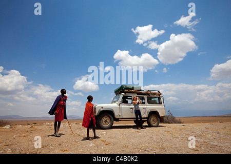 Tanzania, Olduvai. Maasai children watch as a tourist looks out over the landscape around Olduvai gorge. MR. - Stock Image