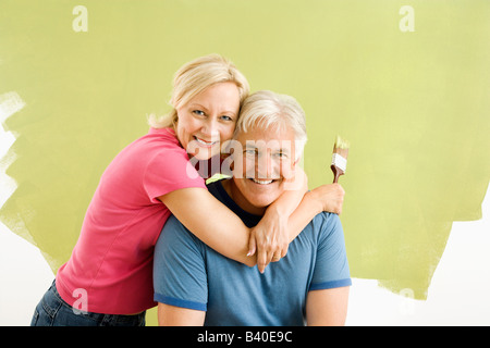 Portrait of smiling adult couple sitting in front of half painted wall with paintbrushes - Stock Image