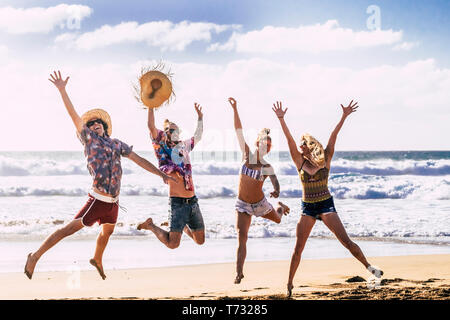 Group of friends caucasian happy couple enjoy the summer holiday vacation running to the water at the beach with coast cliff and blue sky in backgroun - Stock Image