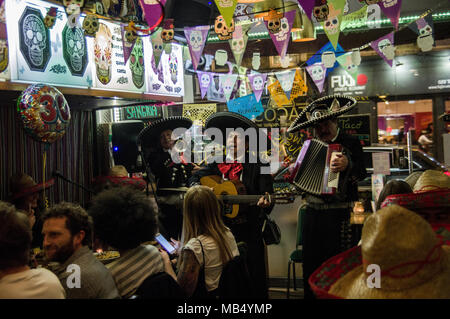 Mariachi players in traditional sombrero hats serenading diners in a mexican restaurant in stoke newington, London, England UK - Stock Image
