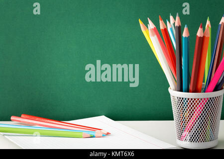 Stack of colorful pencils and open copybook near by on background of blackboard - Stock Image