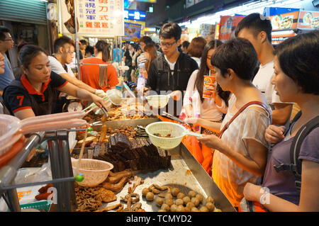 TAIPEI, TAIWAN - JULY 13, 2013: Customers ordering Chinese street food consisting of braised beef and pork entrails in Taipei's Shilin Night Market, t - Stock Image