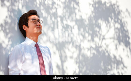 Portrait of businessman relaxing leaning against a wall - Stock Image
