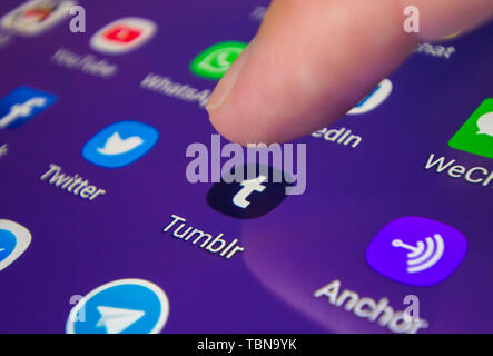 Finger pressing an icon on a smartphone or tablet touchscreen to load the Tumblr microblogging and social media app. - Stock Image