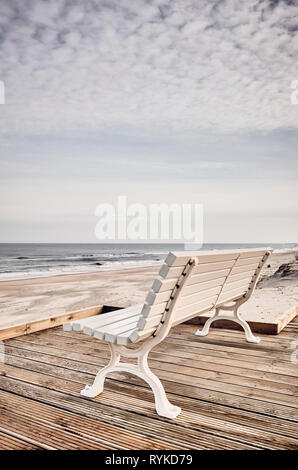 Empty bench on the beachfront, color toned picture. - Stock Image