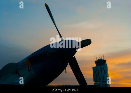 Dawn early morning sunrise romantic scenic on airport P-51D Mustang propeller classic aircraft nose silhouette and - Stock Image