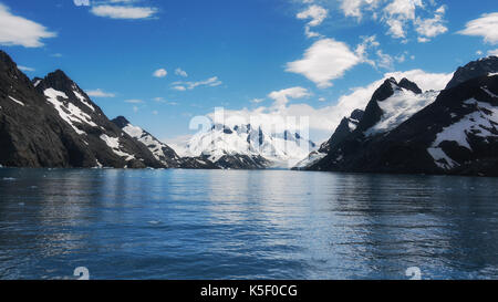View of the steep snow-capped mountains and calm water of the Drygalski Fjord on South Georgia Island, South Atlantic Ocean. - Stock Image