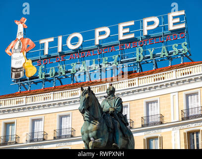 The landmark Tio Pepe sign above Puerta del Sol Square with the statue of Carlos III Charles III of Spain in Madrid - Stock Image