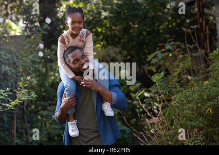 A girl sitting on her fathers shoulders in a garden - Stock Image