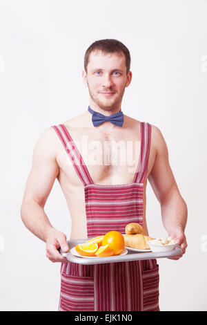 Attractive man in an apron with breakfast on a tray - Stock Image
