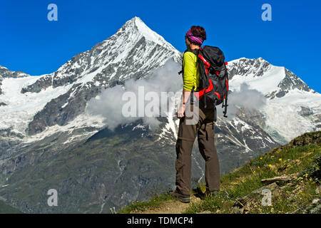 Woman with backpack looking at the Weisshorn peak above the Mattertal valley, Täschalp, Valais, Switzerland - Stock Image
