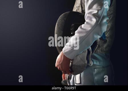 Man fencing, holding mask - Stock Image