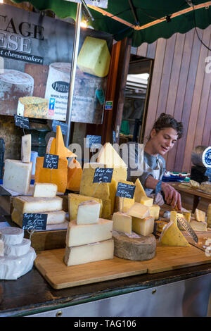 Borough Market Heritage Cheese stall display, with friendly stallholder giving 'try before you buy' tasting samples at Borough Market Southwark London SE1 - Stock Image