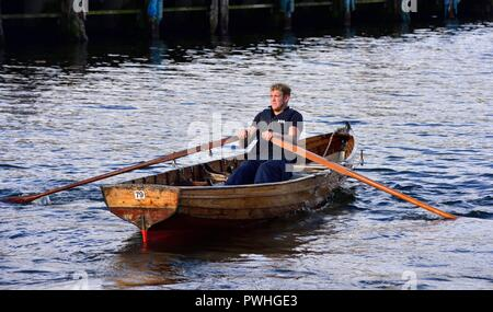 Man rowing a self hire rowing boat on Lake Windermere,Bowness on Windermere,Lake district,Cumbria,England,UK - Stock Image
