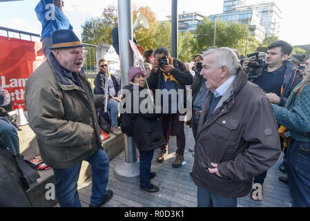 London, UK. 3rd November 2018. Ted Knight (right) confronts Mrtin Smith of Class War  who came to the 'No Demolitions Without Permission' housing protest at City Hall with banners declaring that Labour Councils were the biggest social cleansers in London and 'Labour, Labour Home Snatchers! Even Worse Than Maggie Thatcher', pointing out that it was largely Labour councils who were demolishing council estates so that developers could replace council houses with large numbers of properties sold at high market prices and a miserably small number of homes at social rent, promoting schemes which cut - Stock Image