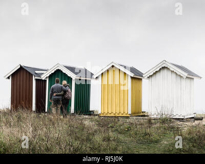 Young couple looking at beach huts - Stock Image