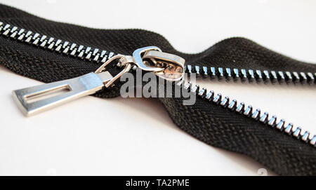 black metal open zipper closeup isolated on white background macro - Stock Image