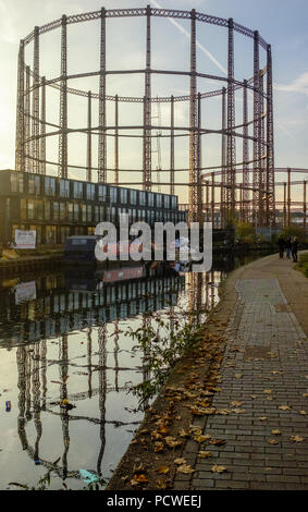 Old Industrial gas holders with modern buildings and Barge, reflecting in Regents Canal Hackney during autumn with leaves on walkway, London, England. - Stock Image