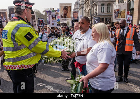 London, UK. 17th April 2019. Knife crime campaigners Operation Shutdown, a consortium of mums, dad's and other bereaved family members and loved ones supported by other campaigners, called for the community to unite and demanded more urgent action by the government to halt the growing epidemic of knife crime. They present two wreaths to the police close to where PC Keith Palmer was murdered before going on to block Westminster Bridge for more speeches. Peter Marshall/Alamy Live News - Stock Image