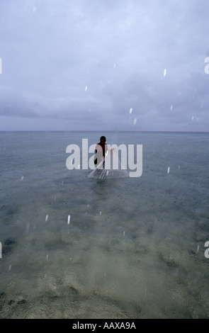 net fisherman in the pacific on shallow reef - Stock Image