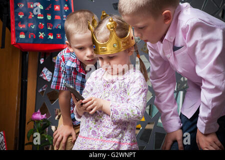 children and smart phone girl carefully considering the smart phone, the girl with the boys carefully consider the - Stock Image