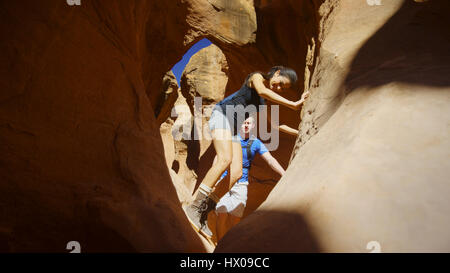 Low angle selective focus view of boyfriend and girlfriend exploring cave in scenic rock formations - Stock Image