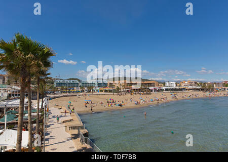Palm trees and beach view Xabia Spain Playa del Arenal beach in summer with blue sky and people, also known as Javea - Stock Image