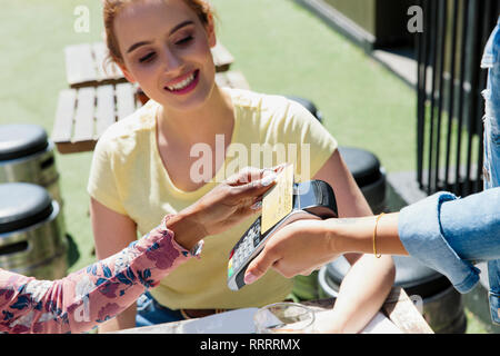 Young woman waitress with smart card at sunny sidewalk cafe - Stock Image